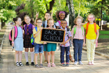 group of multi-racial school children in colorful clothes, carrying school bags and backpacks hold a sign that reads