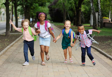 small schoolchildren with colorful school bags and backpacks run to school. Back to schoo