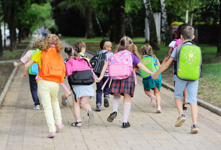small schoolchildren with colorful school bags and backpacks run to school. Zdjęcie Seryjne