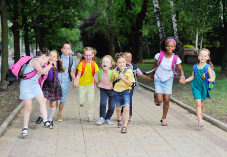 a group of school children of different races in colorful clothes with school bags and backpacks run to school against the background of green m Park.