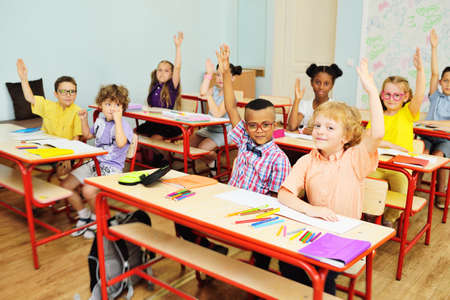 Small children school children smile and hold their hand up for a response against the background of a female teacher and a school class. Back to schoo