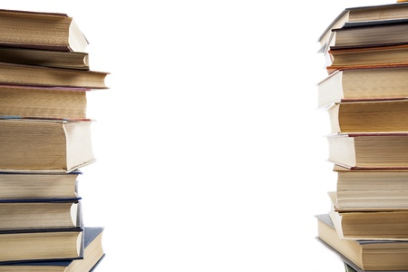 two vertical stacks of old books on a white background photo