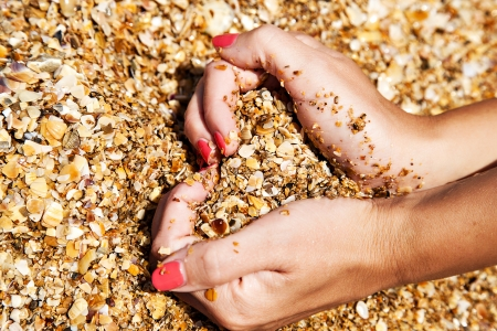 girl holds in the hands of sea sand in the shape of a heart closeup photo