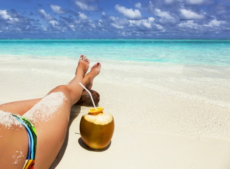 young woman relaxing on the beach with his legs crossed on a coco