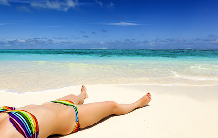 young woman lies on the shore of a tropical sea. on white sand
