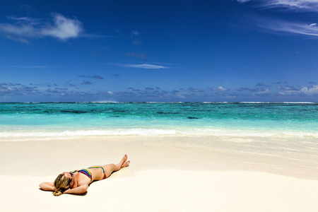 young woman lies on the shore of a tropical turquoise sea
