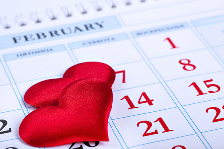 page calendar with two red hearts on the date of February 14 Valentine