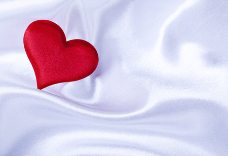 red heart on Valentines Day on a background white silk close up Stock Photo