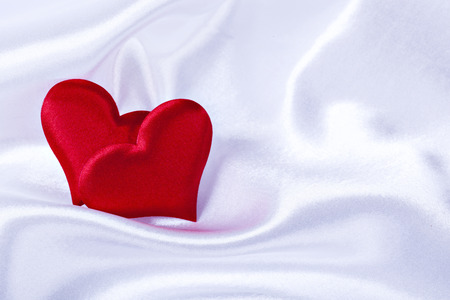 a pair of red hearts for Valentines day on a background white silk close up Stock Photo