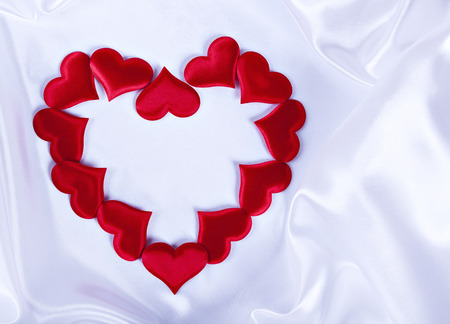small hearts on white silk background laid out in the shape of a big heart