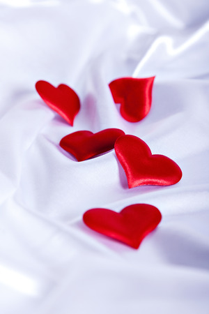 red hearts on white silk background close up