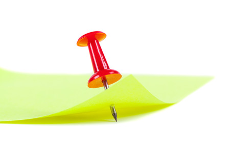 the yellow sheet for notes pierced the red pushpin closeup on white background Stock Photo