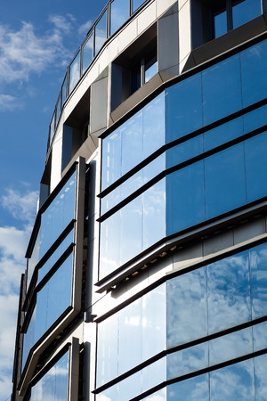blue sky with white clouds reflected in the glass facade of an office high-rise building Stock Photo