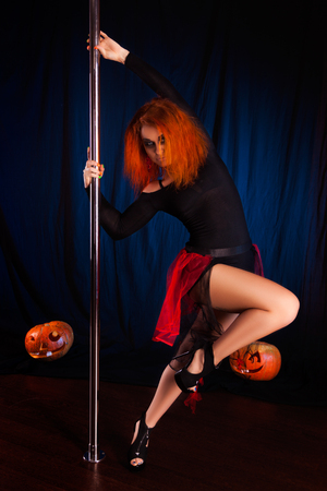 young sexy witch pole dancer on Halloween. Studio photo redhead woman pole dancer