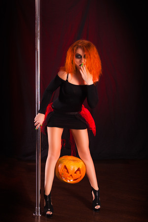 red-haired witch with her hair on Halloween holding a pumpkin. Young sexy girl on holiday wearing a witch costume naughty