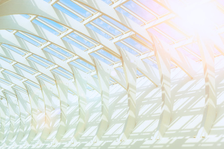 toned photo bearing structure of the glass cover of the building under the blue clear sky Stock Photo
