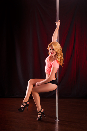 young sexy girl dancer posing pylon on a red background. graceful, flexible model with a gorgeous bum on the pole