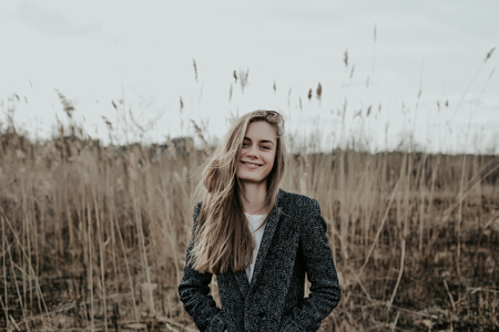 Beautiful blonde woman with long hair in wool coat posing at camera. Girl looking at camera and wide smiling. Background bulrush. Autumn. Outdoor. Medium shot Stock Photo