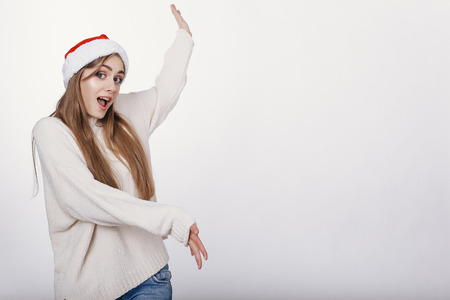 Woman in santa hat pointing on something big. Pretty young model with blonde long hair, wide eyebrows and blue eyes posing on camera in studio on white background. Isolated. Copy space. Place for advertising. Stock Photo