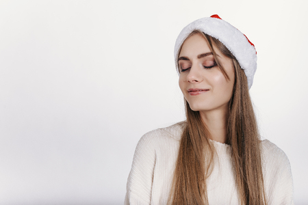 Slim young girl dreaming about christmas. Pretty young model with blonde long hair, wide eyebrows and blue eyes posing on camera in studio on white background. Isolated. Copy space. Place for advertising.