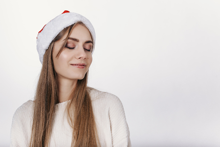 Woman in santa hat dreams about holidays Stock Photo