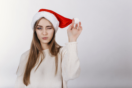 Young european girl winking at camera. Model in santa hat. Christmas. Copy space. Place for advertising.