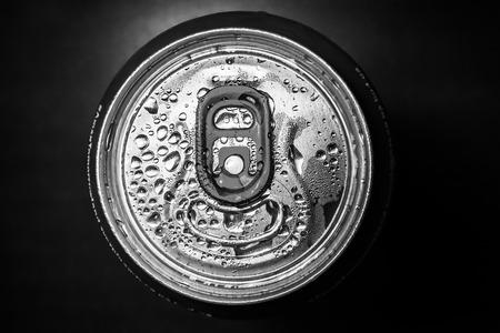 lata de refresco: Aluminum red soda can on black background, black and white