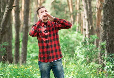strips away: Trendy guy shouting in a pine forest