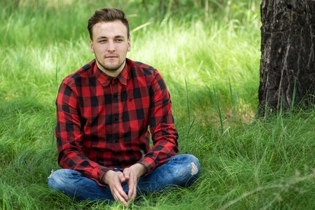 strips away: Trendy guy is smiling and resting on the grass