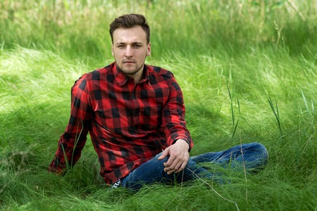 strips away: Trendy guy resting on the grass