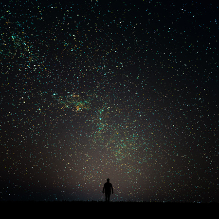 desires: Silhouette of man looking at the stars. The man is on the horizon at night.Man desires guess looking at the stars.