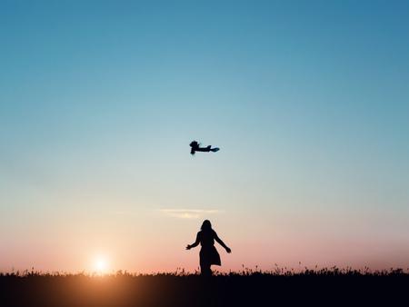 iluminado a contraluz: Silhouette of a beautiful girl jumping over sunset Foto de archivo
