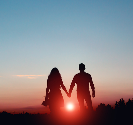 silhouetted: Silhouetted loving couple at sunset. Lovers guy and a girl.
