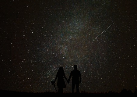 desires: Silhouette of man on a background of stars. Girl desires guess looking at the stars.