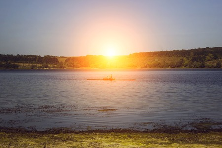 paddles: Man in kayak floating on the river at sunset the sun.