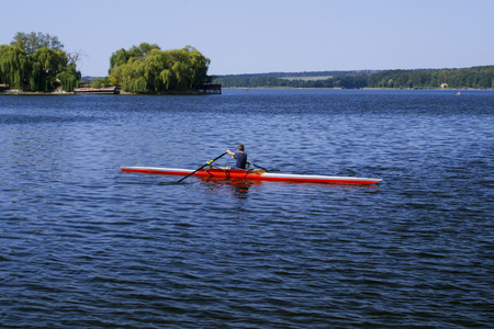 Man in red canoe floating down the river.