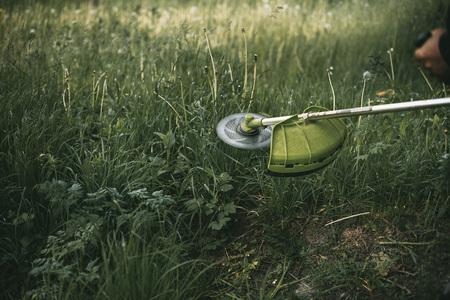 녹색 잔디에 가솔린 트리머 머리입니다. 라운드 트리머 블레이드.