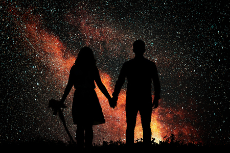 The silhouette of lovers against the backdrop of bright golden star. Love watching the sky. 免版税图像