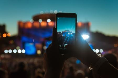 As mãos da silhueta de povos da multidão da audiência usam os telefones espertos que apreciam o concerto. Foto de archivo - 80039575