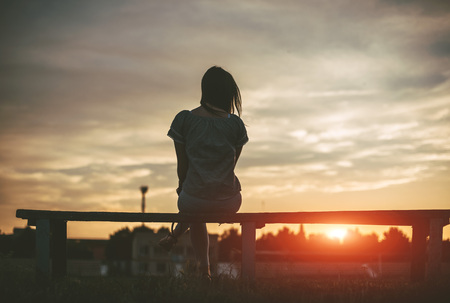 The silhouette of a lonely girl sitting on a bench watching the sunset