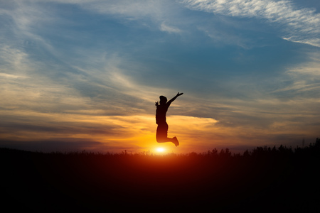 Silhouette of a cheerful man at sunset. Leap at sunset. Stock Photo