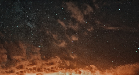 Clouds in the night sky. Starry night Red sky at night. There is noise on the photo.