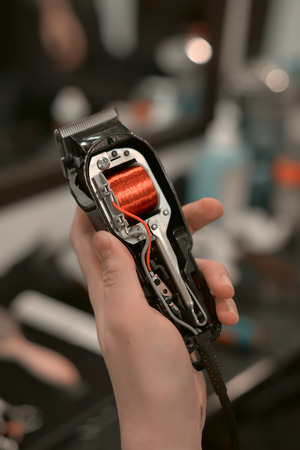 Machine for hairstyles in the hands of barber. Repairing clippers.
