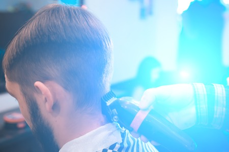 Its time for a new hairdo.The hands of the hairdresser hold a comb and scissors. haircut in the hairdressers.Master hairdresser performs a mans haircut