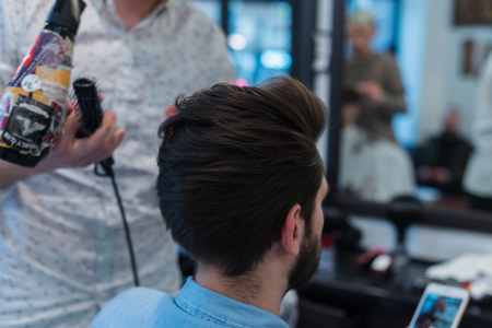 Barber shop. Man in barbers chair, hairdresser styling his hair Stok Fotoğraf