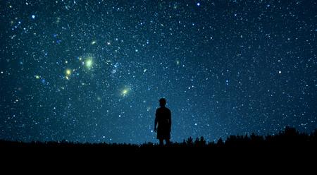 Man kijkt naar de sterren. Alleen mens die sterrenhemel bekijkt. Nachtelijke hemel. Stockfoto