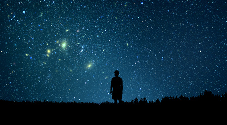 Man kijkt naar de sterren. Alleen mens die sterrenhemel bekijkt. Nachtelijke hemel.