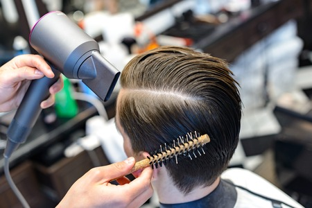 Looking good already. Close up side view of young bearded man getting groomed by hairdresser with hair dryer at barbershop
