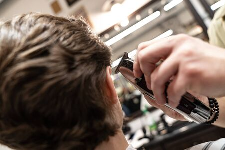 The client receives a haircut in a barbershop. Mens Hair Care. Haircut with scissors Stok Fotoğraf
