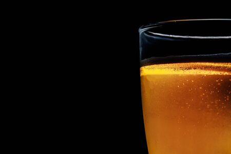 Glass of beer on a dark background. Close-up photo.
